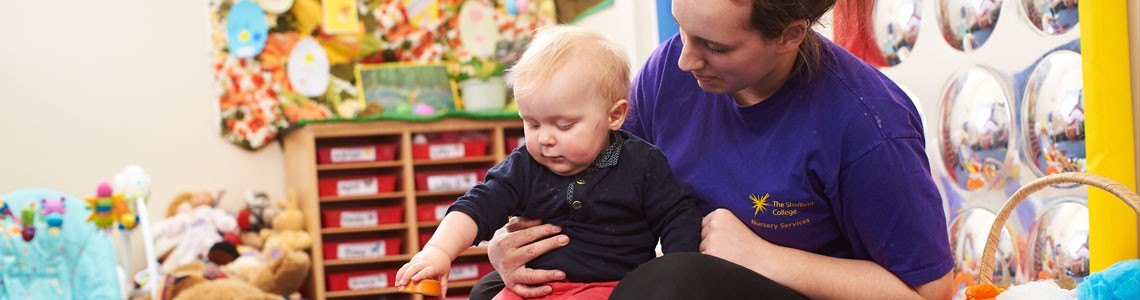 Nursery staff plays with a child